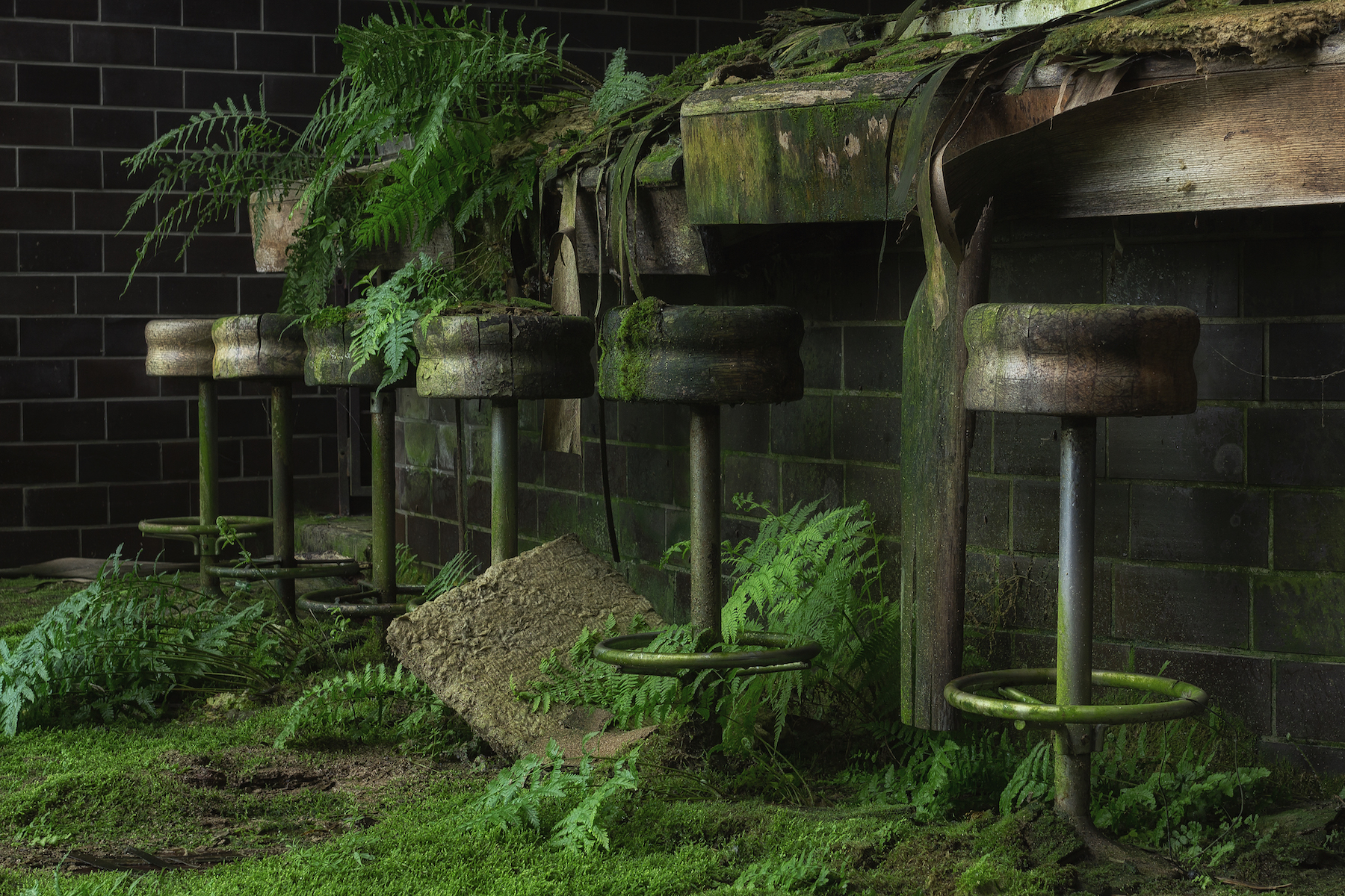 Bar stools in abandoned buildings with grass by Stefan Baumann