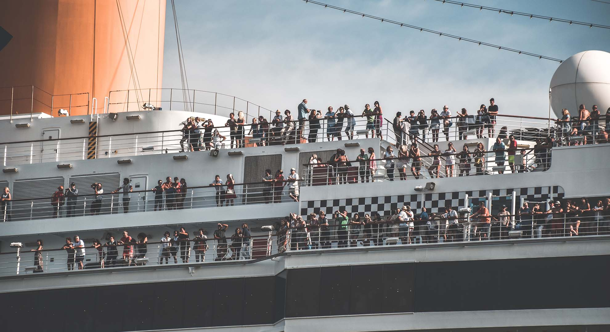 passengers standing on the deck of a cruise