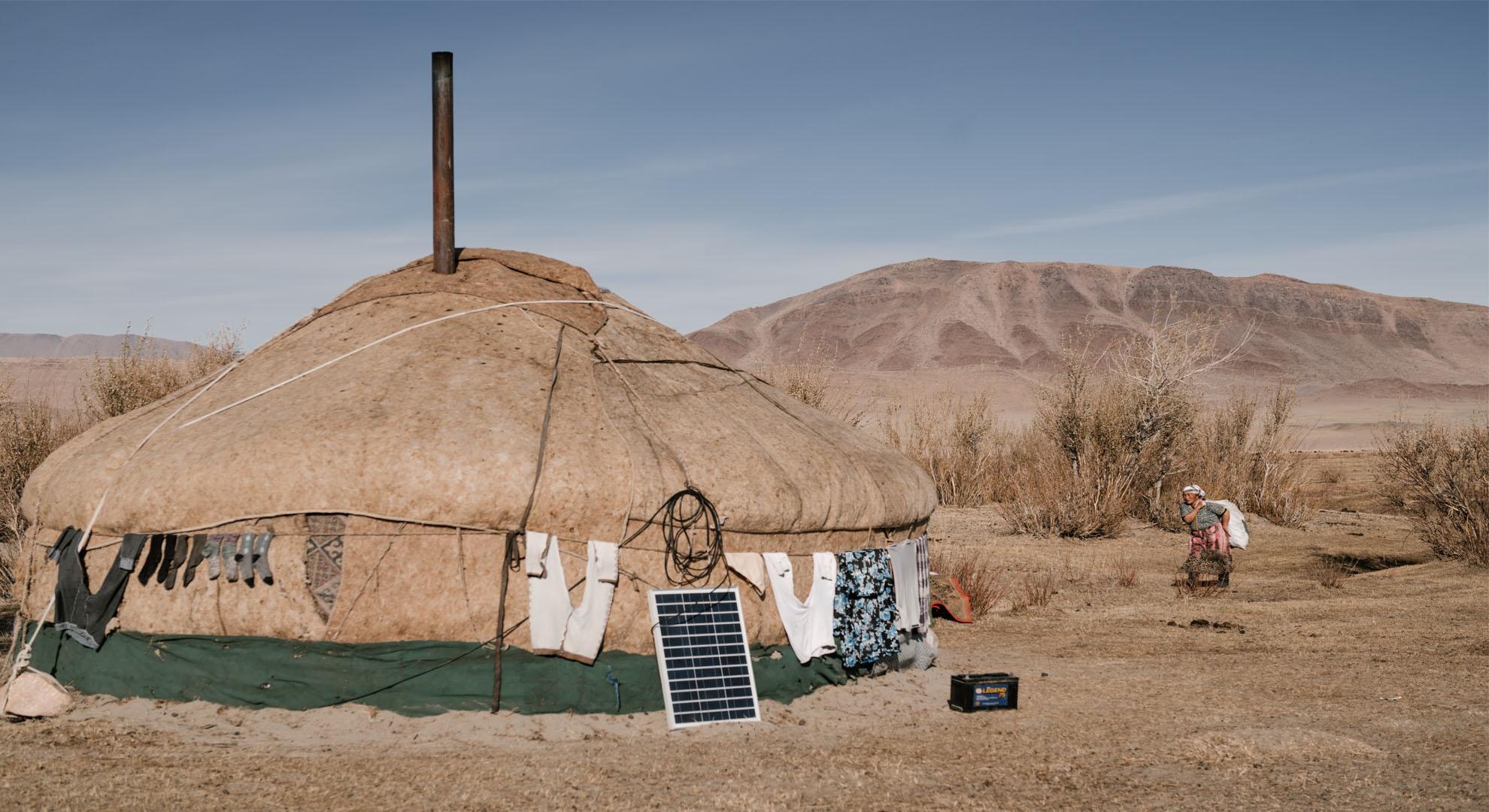 Una mujer entra en una yurta con un panel solar fotovoltaico. © Nick Bonderav/Pexels